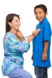 Enfermera de los jóvenes que controla al muchacho Fotografía de archivo libre de regalías