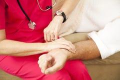 Enfermera de salud casera - tomar pulso Imagen de archivo