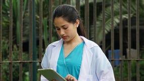 Enfermera de sexo femenino adolescente hispánica With Tablet Imagen de archivo libre de regalías