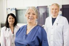Enfermera de sexo femenino confiada Smiling With Doctors en clínica fotografía de archivo libre de regalías