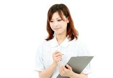Enfermera de sexo femenino joven con el sujetapapeles Imagenes de archivo