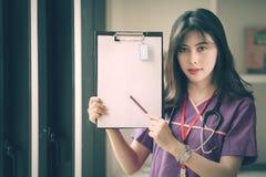 Enfermera de sexo femenino joven que sostiene el lápiz y que muestra su tablero imagen de archivo