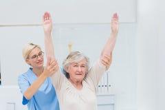Enfermera de sexo femenino que ayuda al paciente femenino en el ejercicio Foto de archivo