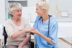 Enfermera de sexo femenino que comprueba la flexibilidad de la muñeca de los pacientes Imagen de archivo