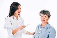 Enfermera de sexo femenino que quiere tomar la temperatura del paciente Foto de archivo libre de regalías