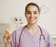 Enfermera de sexo femenino que sostiene hacia fuera la botella de medicación imagenes de archivo