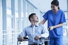 Enfermera de sexo femenino sonriente que empuja y que ayuda al paciente en una silla de ruedas en el hospital Foto de archivo