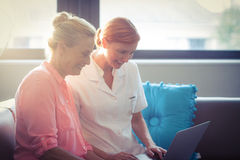 Enfermera de sexo femenino y mujer mayor que usa el ordenador portátil Fotos de archivo libres de regalías
