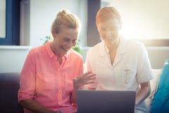 Enfermera de sexo femenino y mujer mayor que usa el ordenador portátil Fotos de archivo
