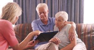 Enfermera de sexo femenino y pares mayores que obran recíprocamente con uno a almacen de metraje de vídeo
