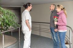 Enfermera de sexo masculino con dos visitantes en un pasillo fotografía de archivo libre de regalías