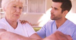 Enfermera de sexo masculino que ayuda a la mujer mayor para ejercitar en el patio trasero metrajes