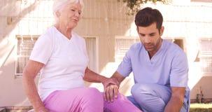Enfermera de sexo masculino que ayuda a la mujer mayor para ejercitar en el patio trasero almacen de metraje de vídeo