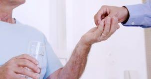 Enfermera de sexo masculino que da píldoras al hombre mayor almacen de metraje de vídeo