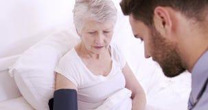 Enfermera de sexo masculino que mide la presión sangrienta a la mujer mayor metrajes