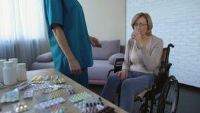 Enfermera del hospital que da la medicina al paciente femenino en rutina del tratamiento de la silla de ruedas metrajes