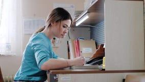 Enfermera del paramédico de servicio en la tabla que hace papeleo almacen de metraje de vídeo