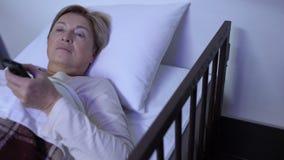 Enfermera descortesa que toma el control remoto de la TV del lecho de enfermo de mentira del viejo paciente femenino almacen de metraje de vídeo