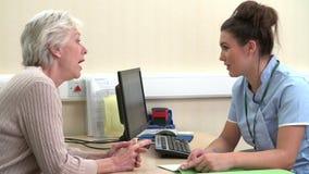 Enfermera Discussing Test Results con el paciente femenino mayor almacen de video