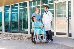Enfermera And Doctor Looking en el paciente en la silla de ruedas fotos de archivo libres de regalías