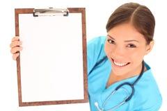 Enfermera/doctor que muestra la muestra en blanco del sujetapapeles Fotografía de archivo libre de regalías