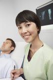 Enfermera feliz With Men Lying en cama Imagenes de archivo