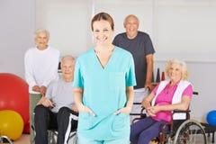 Enfermera geriátrica delante del grupo de gente mayor fotografía de archivo libre de regalías