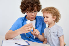 Enfermera Giving Vitamins al pequeño niño Imágenes de archivo libres de regalías