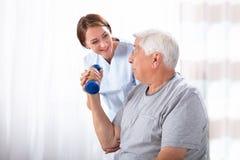 Enfermera Helping Senior Man con ejercicio de la pesa de gimnasia foto de archivo libre de regalías