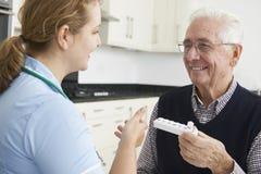 Enfermera Helping Senior Man con la medicación Imágenes de archivo libres de regalías