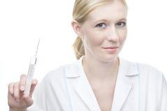 Enfermera hermosa de los jóvenes con la jeringuilla Fotografía de archivo libre de regalías