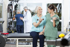 Enfermera Instructing Senior Patient que ejercita con pesa de gimnasia imagen de archivo