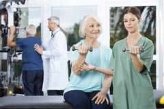 Enfermera Instructing Senior Woman que ejercita con pesa de gimnasia imagen de archivo