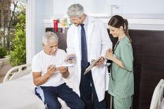 Enfermera Looking At Doctor que explica la prescripción al paciente imágenes de archivo libres de regalías