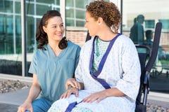 Enfermera Looking At Patient que se sienta en la silla de ruedas en imágenes de archivo libres de regalías