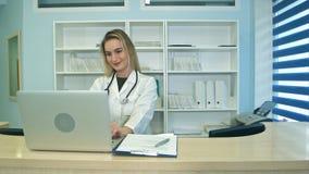 Enfermera médica sonriente que trabaja en el ordenador portátil y la fabricación de notas en el mostrador de recepción Imagen de archivo libre de regalías
