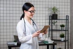 Enfermera m?dica de sexo femenino joven que usa la tableta en oficina del hospital fotografía de archivo