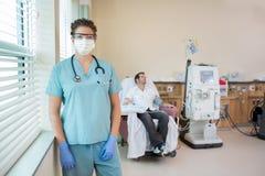 Enfermera In Protective Clothing con el paciente Foto de archivo