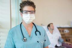 Enfermera In Protective Clothing con el paciente adentro Imagen de archivo libre de regalías