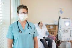 Enfermera In Protective Clothing mientras que paciente Imagenes de archivo