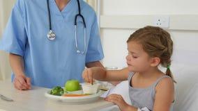 Enfermera que alimenta a la niña enferma en cama metrajes