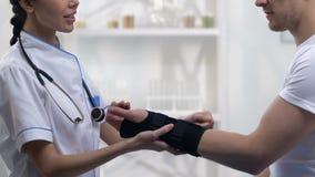 Enfermera que aplica el apoyo de la muñeca del titán al paciente masculino sonriente, tratamiento médico almacen de metraje de vídeo