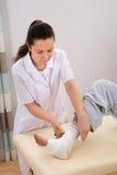 Enfermera que ata el vendaje en el pie del hombre Fotos de archivo