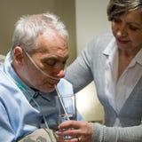 Enfermera que ayuda al hombre enfermo mayor con la consumición Imágenes de archivo libres de regalías