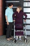 Enfermera que ayuda a la mujer mayor con el caminante Imagen de archivo