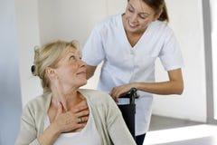 Enfermera que ayuda a la mujer mayor en el hospital foto de archivo libre de regalías