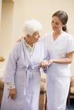 Enfermera que ayuda a la mujer mayor a recorrer Fotografía de archivo libre de regalías
