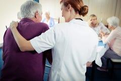 Enfermera que ayuda a un mayor que usa a un caminante Fotos de archivo libres de regalías