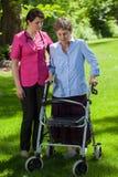 Enfermera que camina al lado de mujer con el caminante ortopédico Foto de archivo libre de regalías