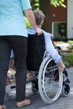 Enfermera que camina con la mujer mayor en la silla de ruedas Fotos de archivo libres de regalías